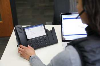Person working in an office using a phone system